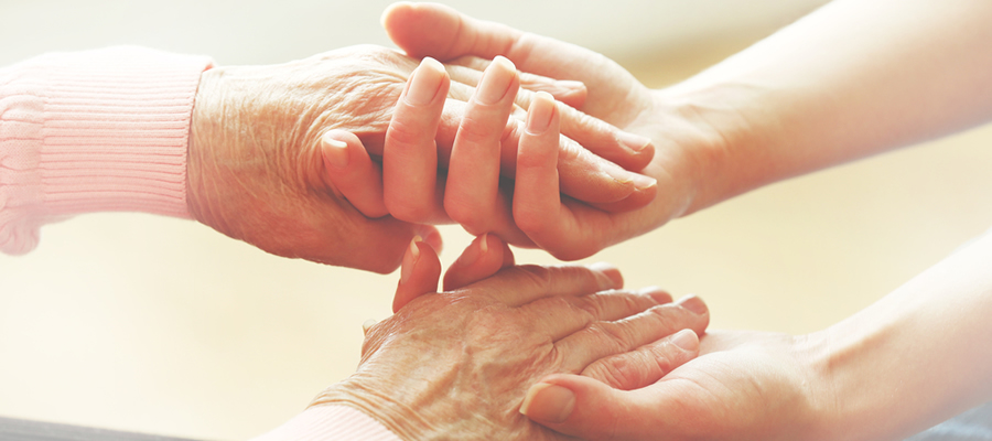 An older person's hand being held by a younger person.